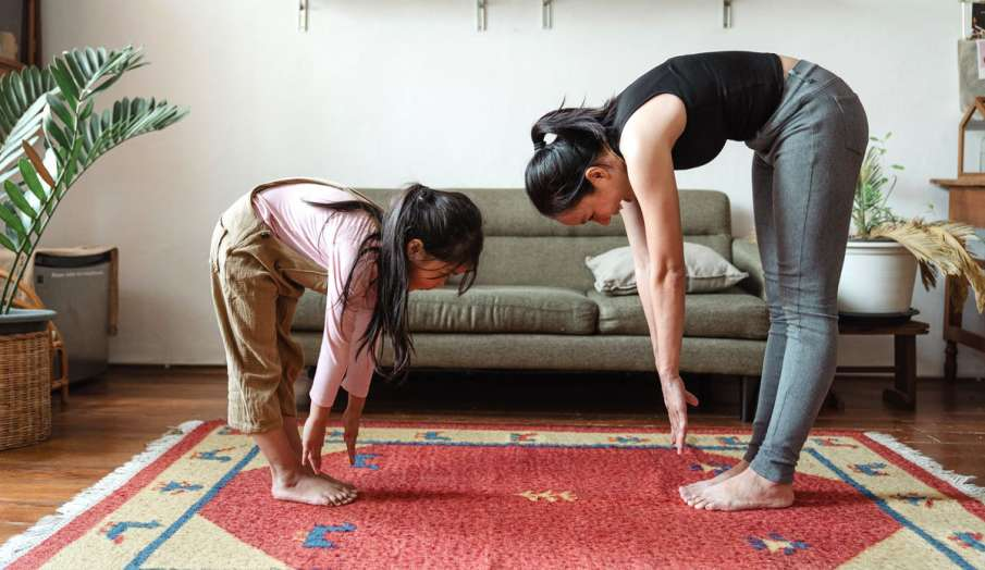 mom and daughter doing yoga exercise